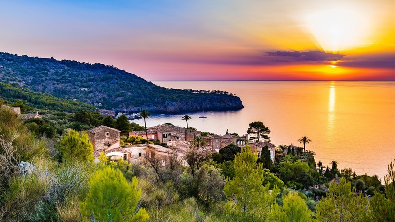 Beautiful sunset at the coast of Majorca Spain island, quaint village at the seaside of Deia, Mediterranean Sea, Balearic islands.