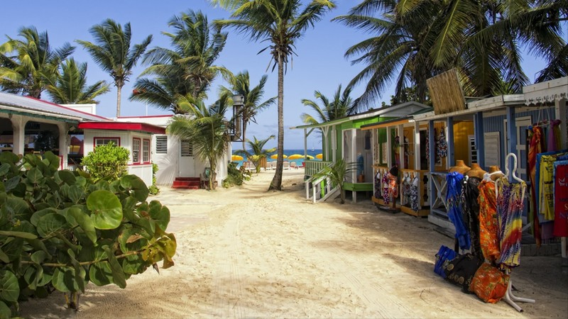 A street full of street vendors leading to a beach on a Caribbean Island