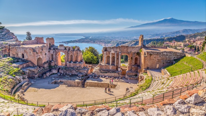 Ruins of the Ancient Greek Theater in Taormina, Sicily with the double smoke tail of the Etna extending over the the Giardini-Naxos bay