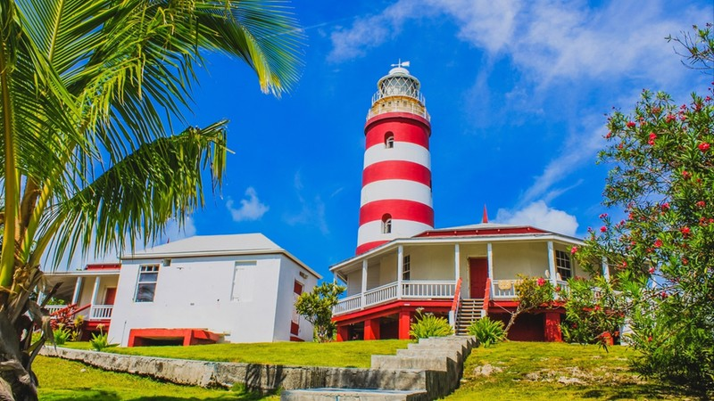 The iconic Elbow Reef Lighthouse with bright beautiful blue sky in the background. Hope Town, Marsh Harbour, Abaco, The Bahamas.