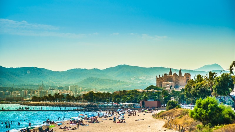View of the beach of Palma de Mallorca with people lying on sand and the gorgeous cathedral building visible in background
