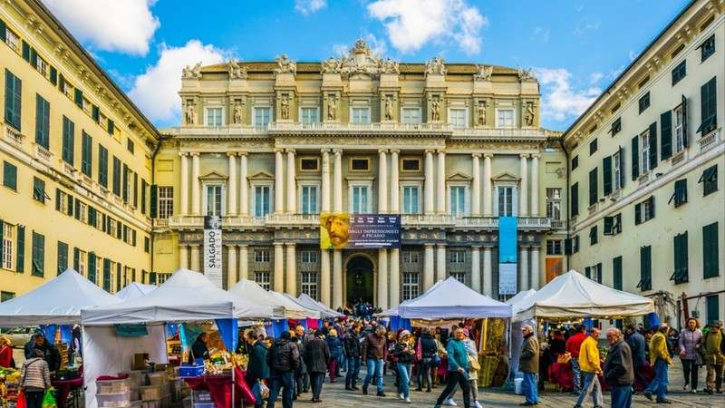 People are enjoying sunny day on the square raffaele de ferrari in front of the palazzo ducale Genoa, Italy