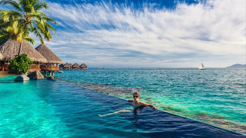 Young woman in the infinity pool in exotic island resort with bunalows over water