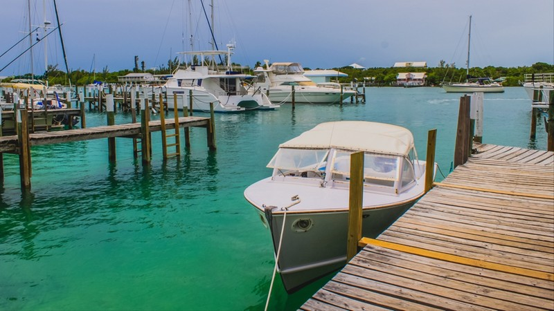 Boats moored inside a marina bay with small wooden pier at Man O War cay, Abaco, The Bahamas