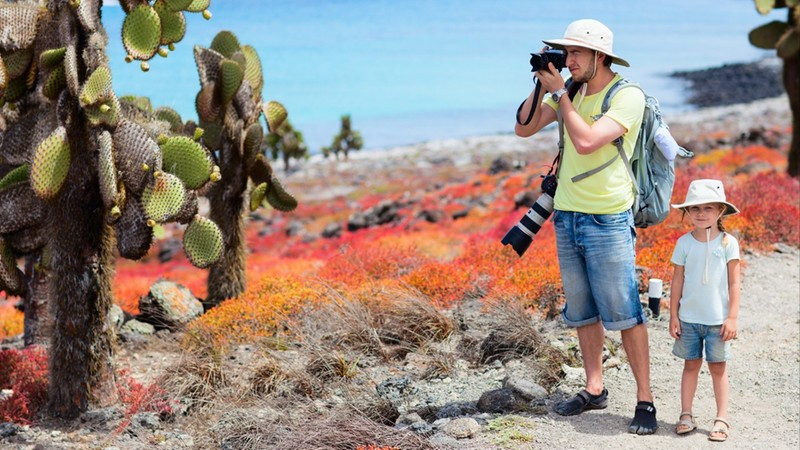 Father and daughter at scenic terrain on Galapagos South Plaza island